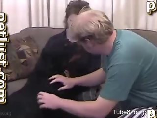 Two dirty men are playing with a big black doggy